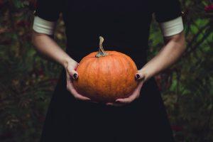 a girl holding a pumpkin