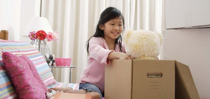 Little girl packing a teddy bear in moving box