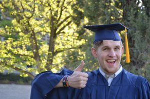 A man in a graduation gown showing a thumbs up