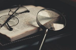 A magnifying glass and spectacles on a book