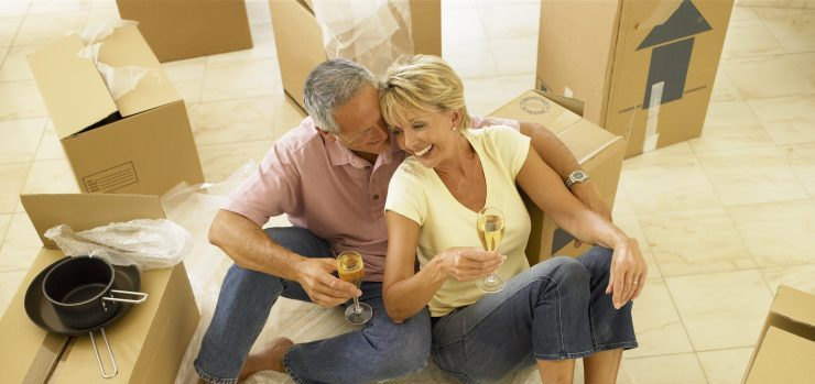 Couple with moving boxes waiting for senior moving CA experts