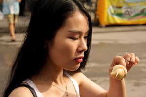a woman eating on the street