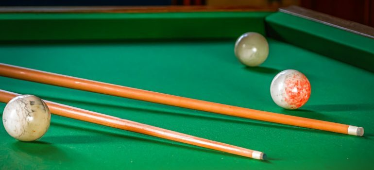 Pool table and sticks up close.