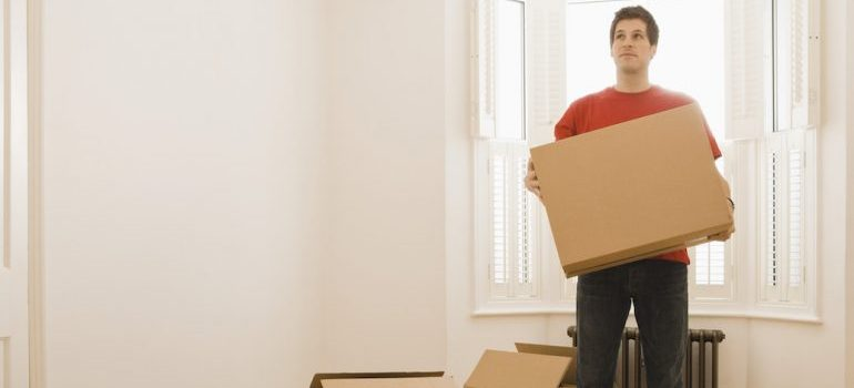 Man with boxes in new home- Moving from California to Washington