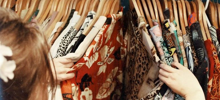 A person looking through clothes - downsize the wardrobe when decluttering your child's bedroom