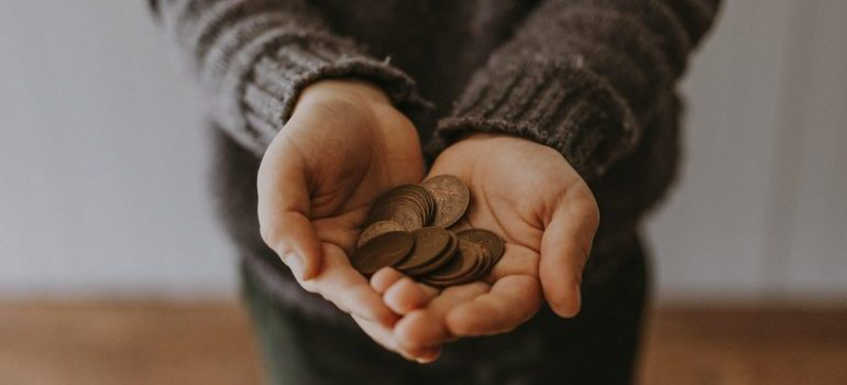 A person with coins in their hands - start saving money for moving out of your parents' home