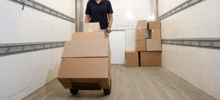 A woman loading the moving truck - the type of moving services that will be most helpful is full-service moving
