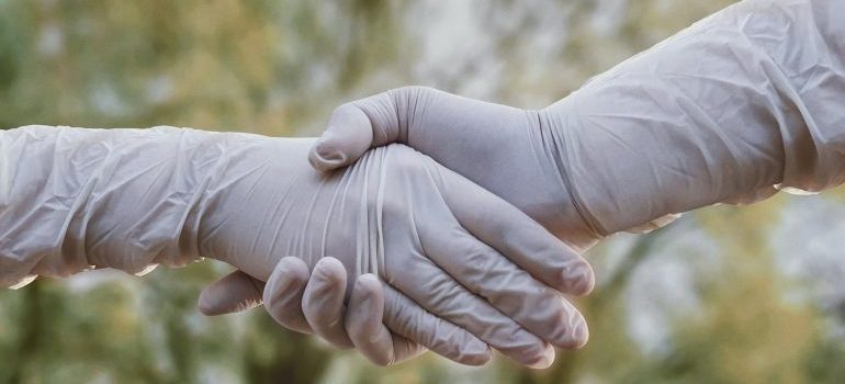 People with gloves shaking hands