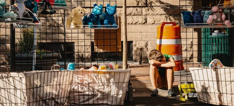 boy selling his stuffed toys on the pavement