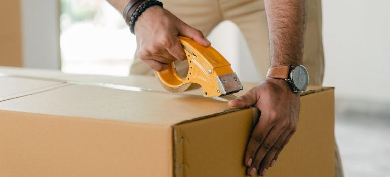 a man taping a box - moving services seattle