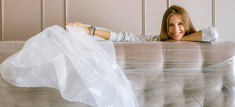 woman unpacking couch that furniture movers Denver transported
