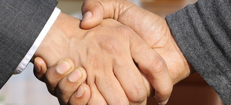 people shaking hands when planning a family move to Seattle