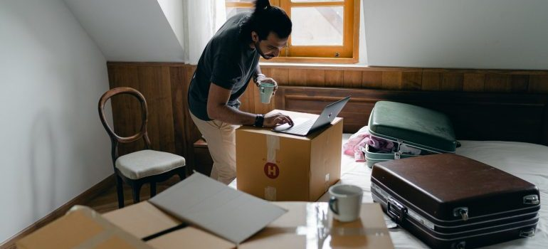 man with laptop surrounded by boxes