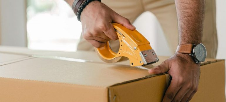 man closing a cardboard box
