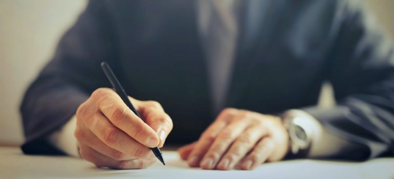 man holding a pen above a paper