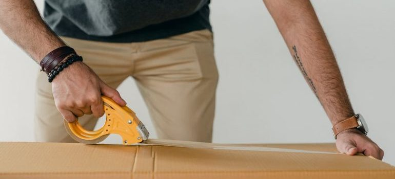 man taping a cardobard box