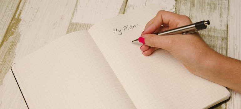 Woman writing a plan in a notebook