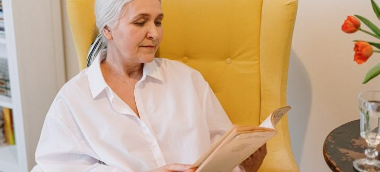 woman sitting and reading while she thinks shoudls he move as an empty nester from LA