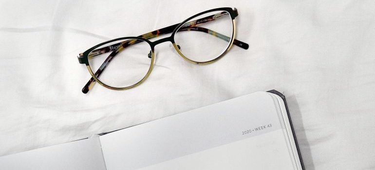 Glasses and a planner on a bed