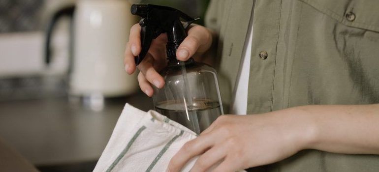 person-in-green-button-up-shirt-holding-cleaning-supplies