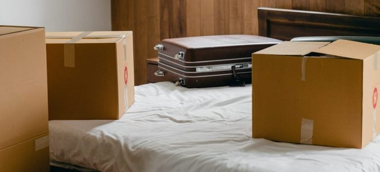 carton-boxes-and-suitcases-placed-on-bed-in-empty-light-room