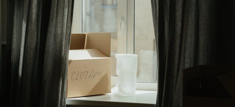 """box labeled """"clothes"""" on the window"""
