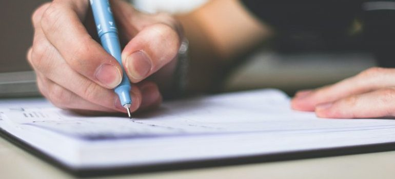 person-holding-blue-ballpoint-pen-writing-in-notebook