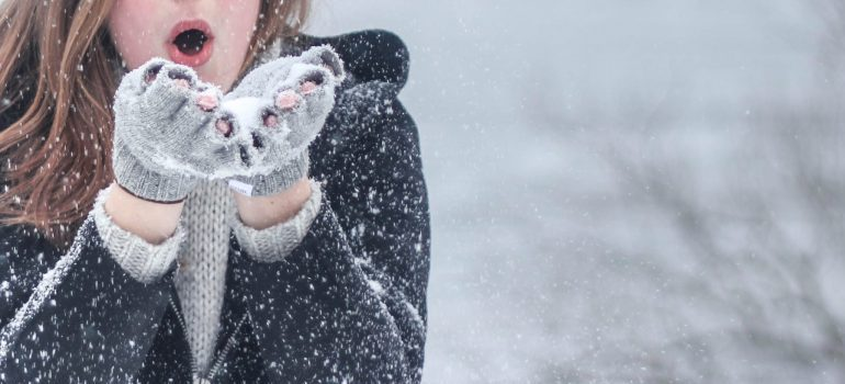 woman wearing gray gloves, snowing