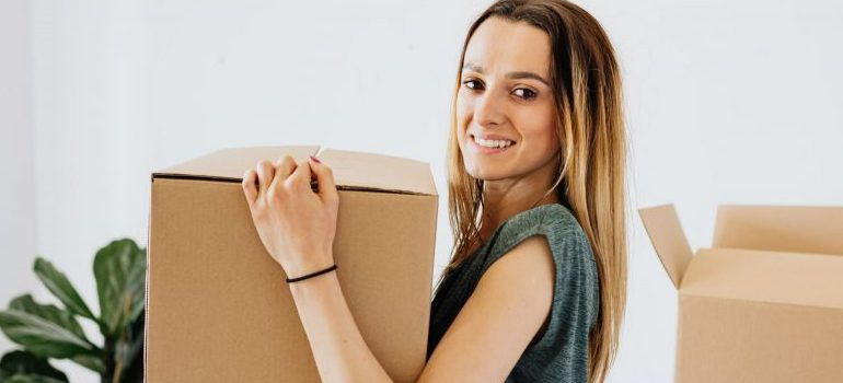female carrying cardboard box