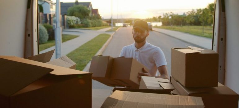 male placing cardboard boxes in the moving van