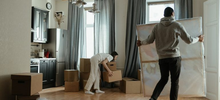 A man and woman carrying things in the house