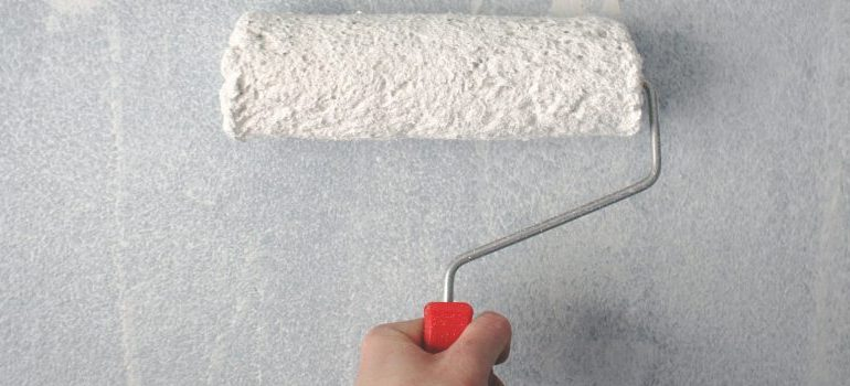 person painting the wall