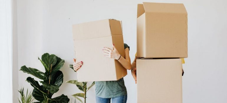 woman and man holding moving boxes