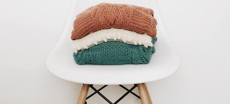 three sweaters on the chair