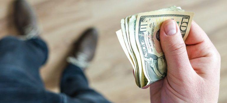 person holding dollar bills in hand