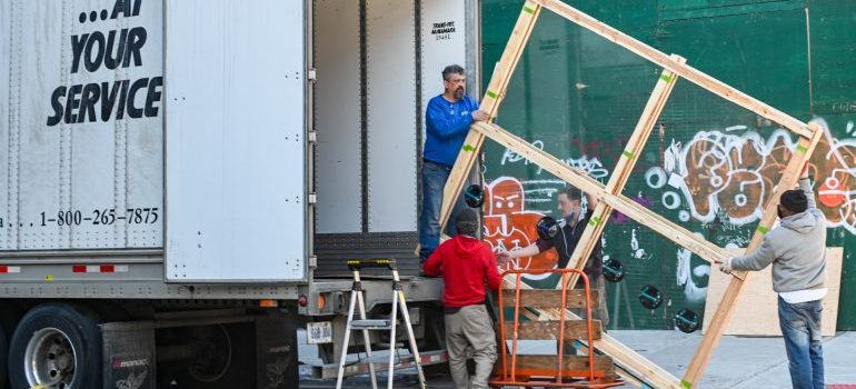 three men putting wooden frame in the truck
