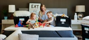 A woman and her kids sitting on a bed and packing