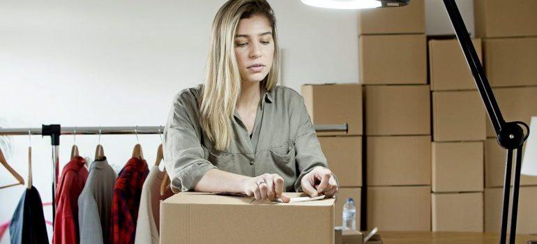 A woman packing a cardboard box.