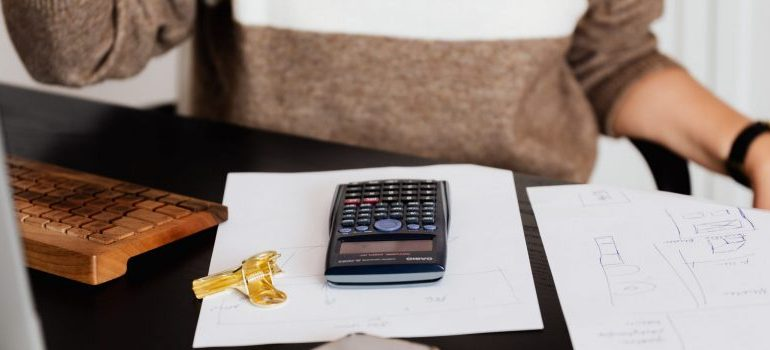 person sitting, calculator on the table