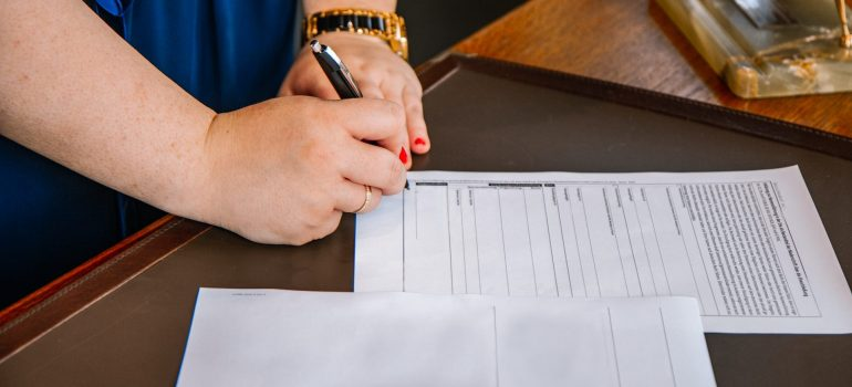 Woman with a wristwatch and wedding ring is standing beside the desk ready to sign a moving contract