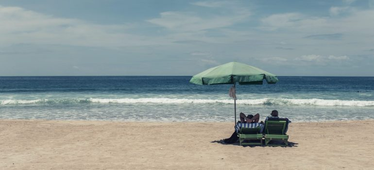 A couple on the sandy beach seating under parasol on beach loungers and watching waves on the ocean in front of them
