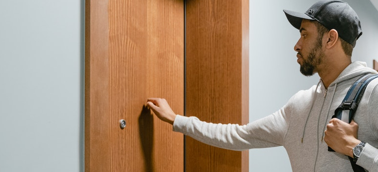 a person knocking on the door as a way to meet your neighbors after moving to LA