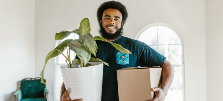A mover carrying a box and a plant