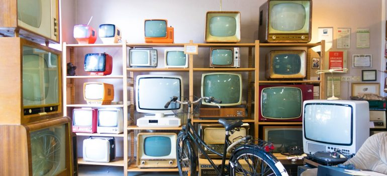 Place with lot of old TV sets on shelfs and bicycle in front of them, you find when moving a TV into storage.
