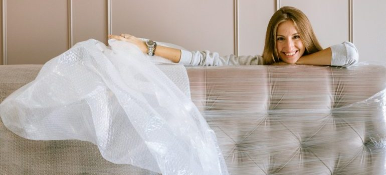Woman wrapping her couch.