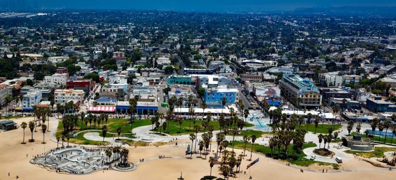 Sand of the Venice Beach in the front with LA houses reaching far away towards the horizon.