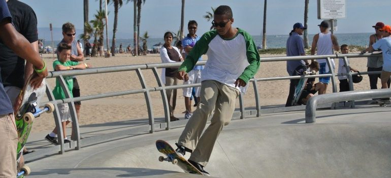 A boy with sunglasses is on the skateboard, in the area protected by railing, while people are watching him and the whole family enjoy August in LA.