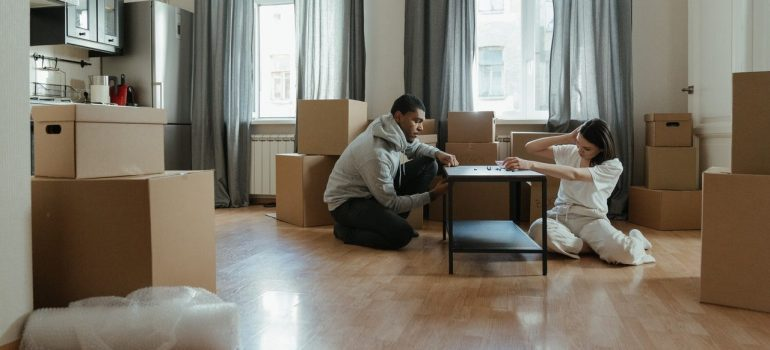 a couple disassembling a coffee table on the kitchen floor