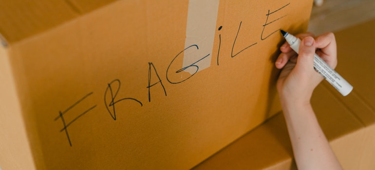 Person writing Fragile on box