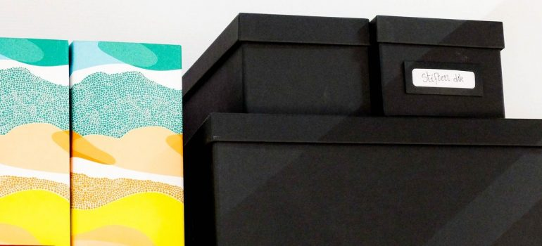 three black boxes besides two colorful boxes